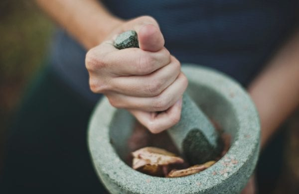 a hand grounds compounds with a pestle