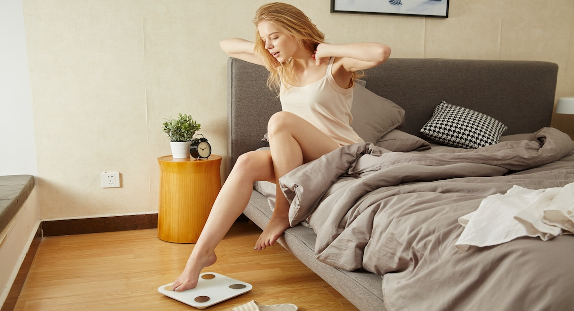 woman in bed stepping on a scale