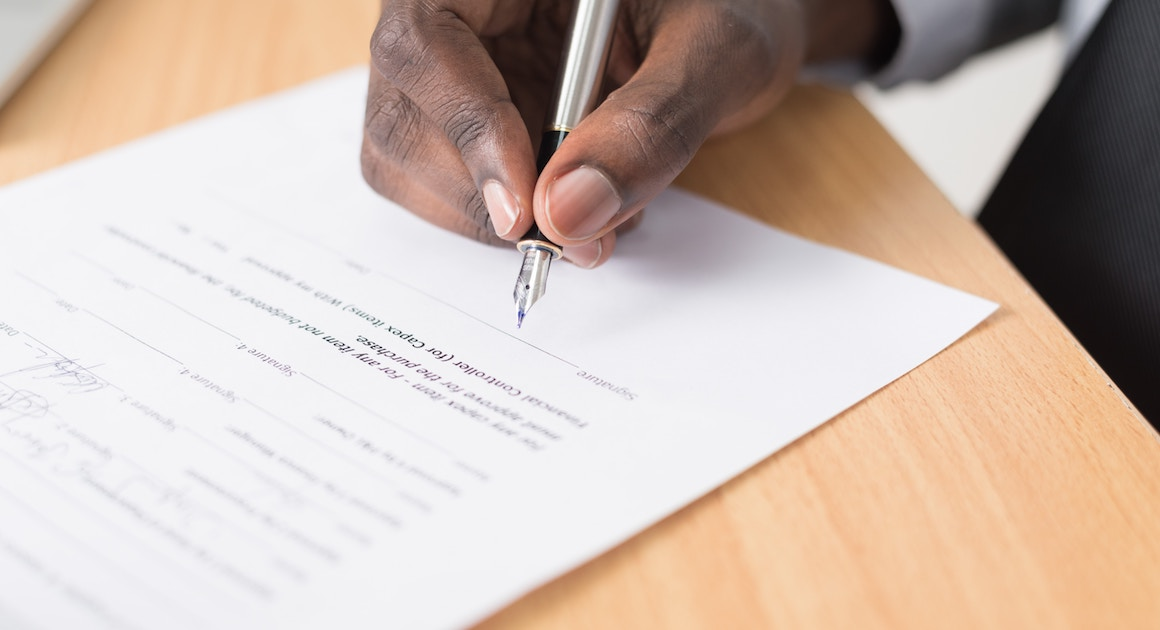 hand signing a contract with a pen