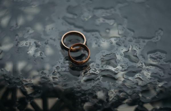 two wedding rings lying in a puddle of water