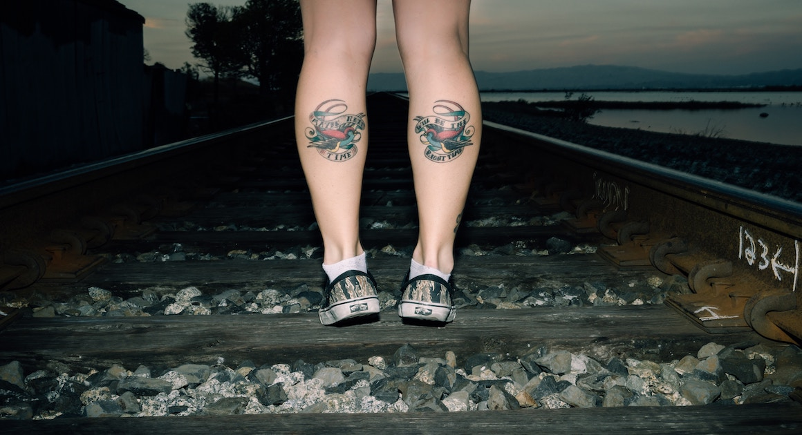 woman facing away on train tracks with tattoos