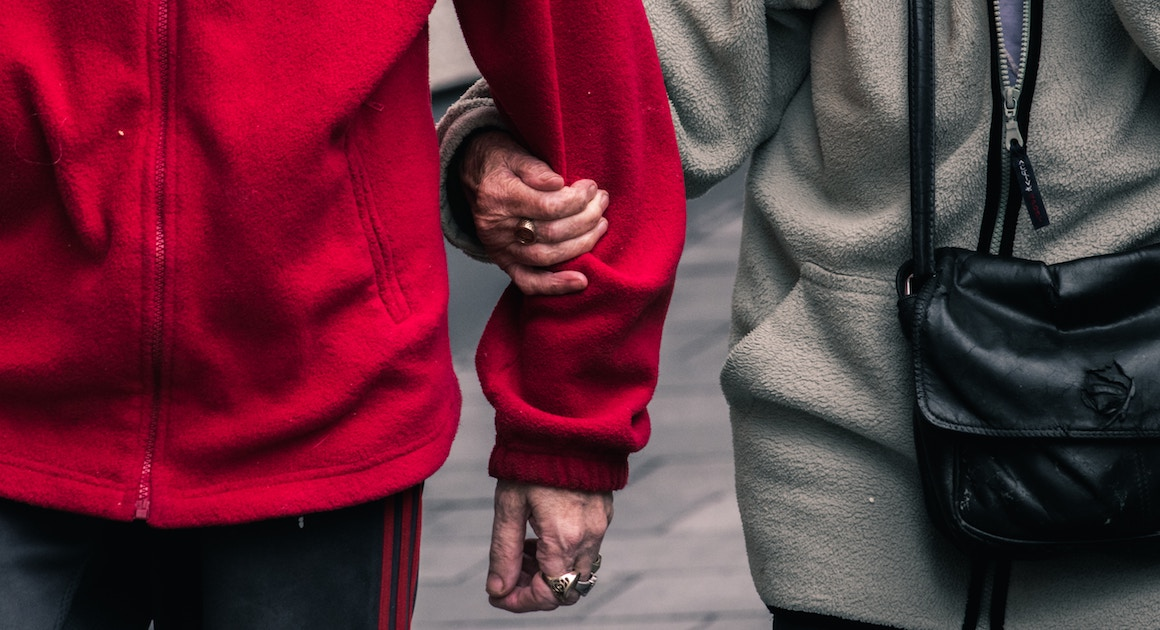 two elderly people supporting each other by the arm