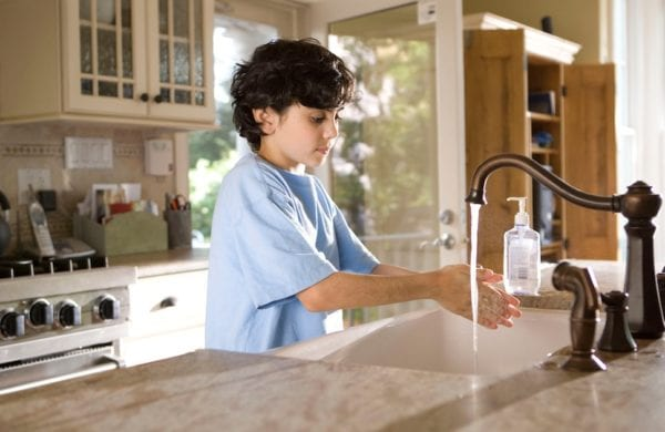a boy washes his hands in the kitchen sink