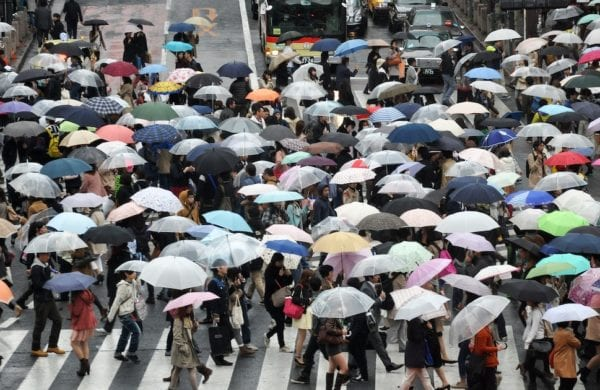 crowd of people walking with umbrellas