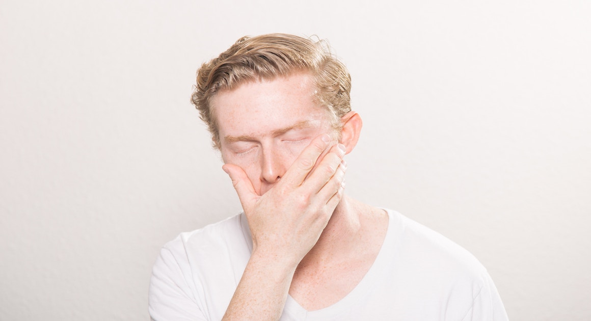 man covering his mouth in frustration