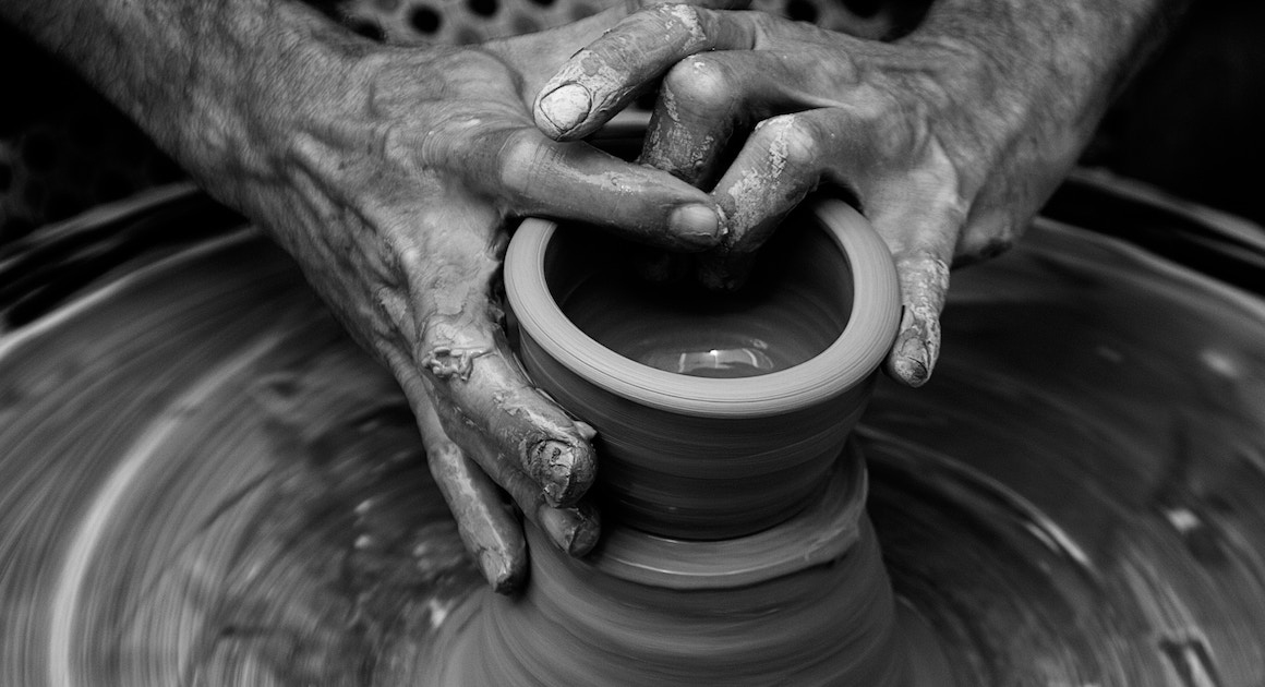 hands shaping a clay bowl