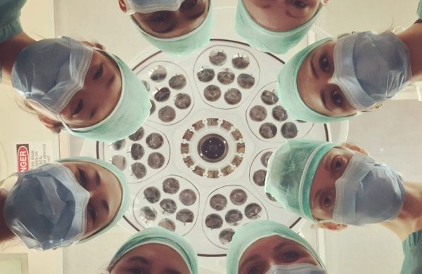 doctors in a circle looking down at a patient
