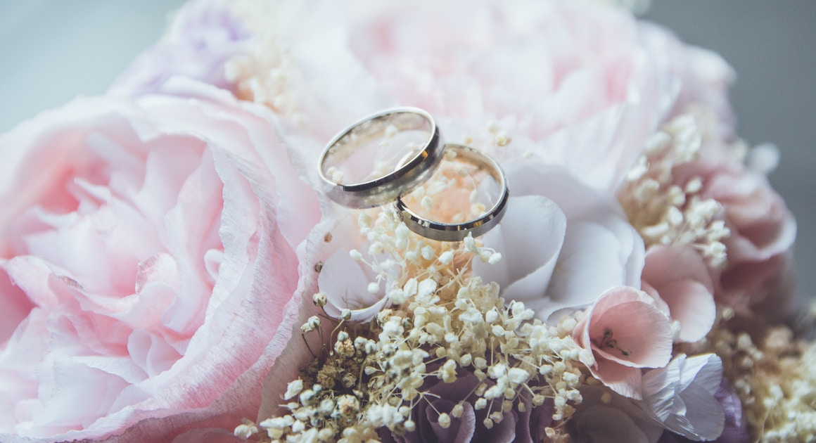 two wedding rings on a floral arrangement