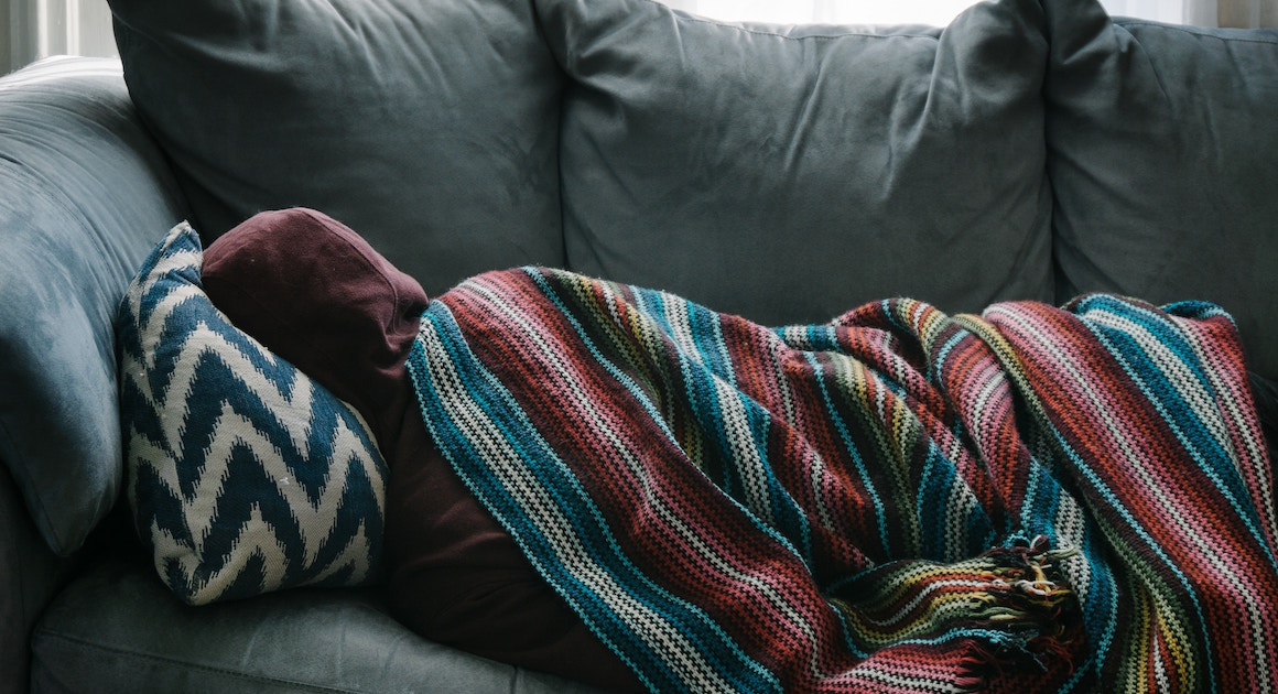sick person lying on a couch