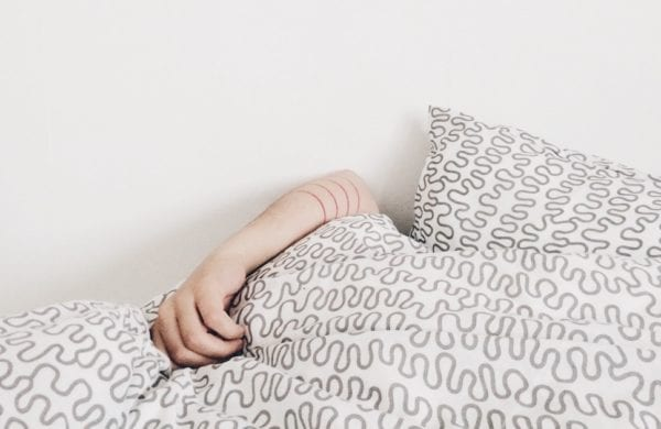 arm of a sick person under covers