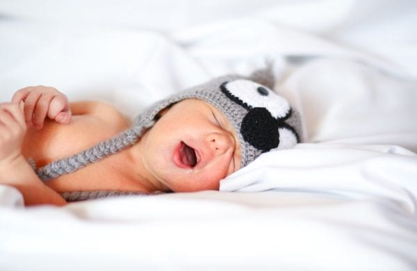 snoring infant wearing a hat in bed