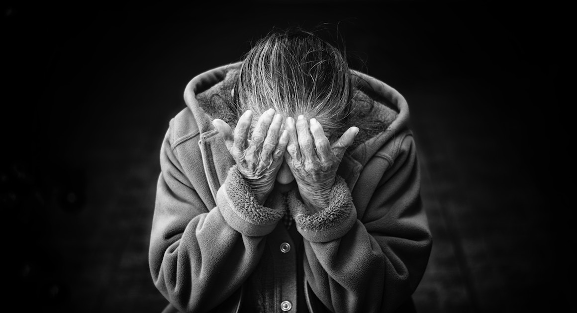 an old woman holds her head in her hands