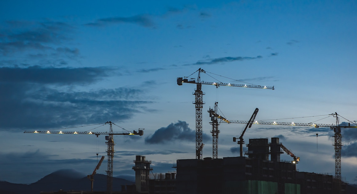 a series of cranes at a construction site
