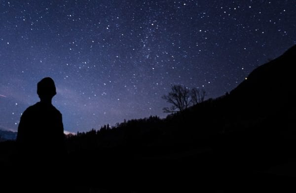 man in silhouette looking at the night sky