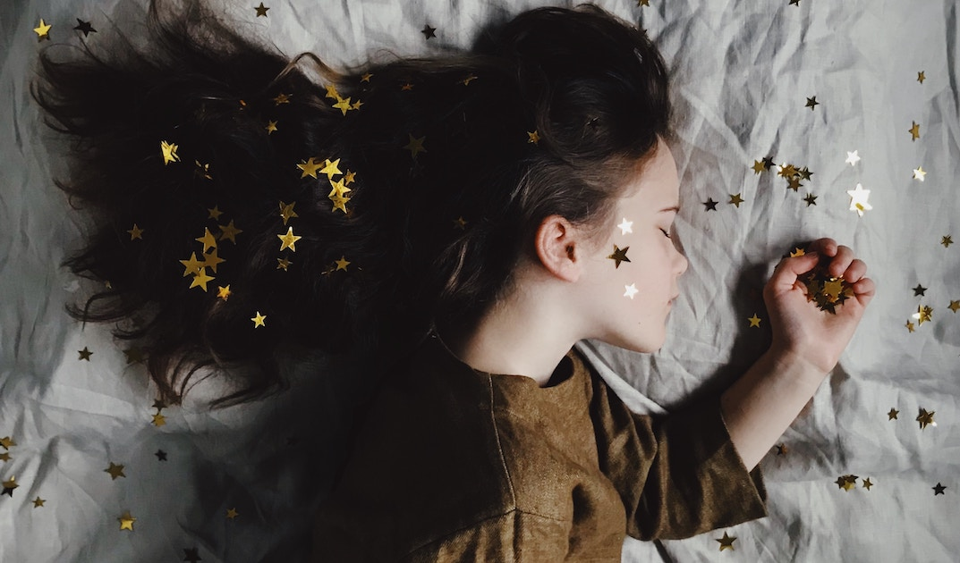 sleeping girl on a bed with stars in her hair