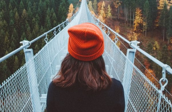 a woman looks out over a narrow bridge