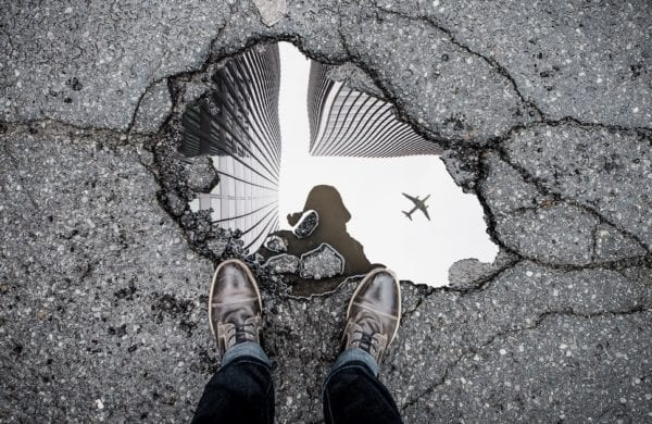 two feet look down at a crack in the street