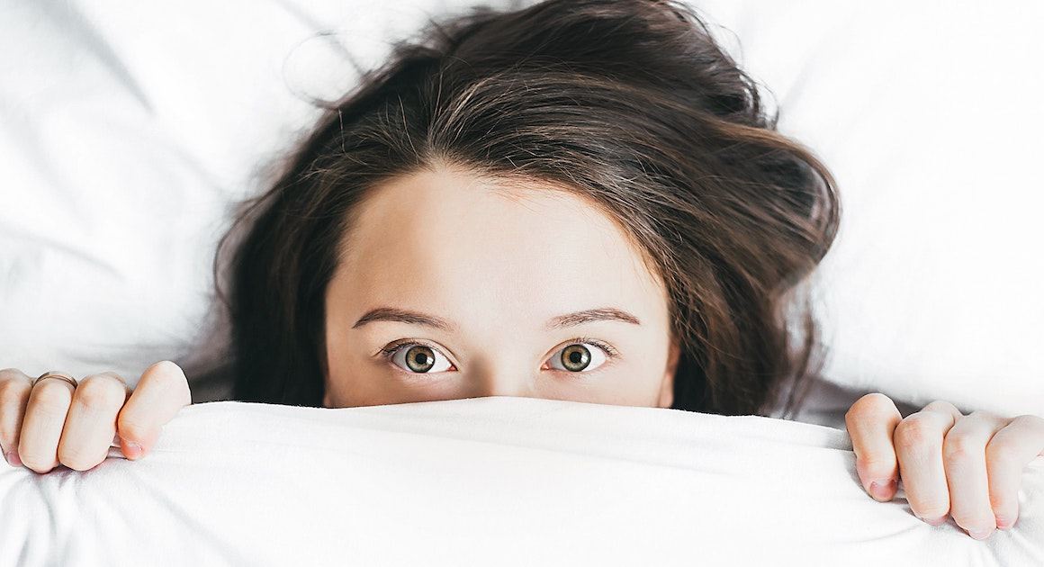 woman hiding under covers
