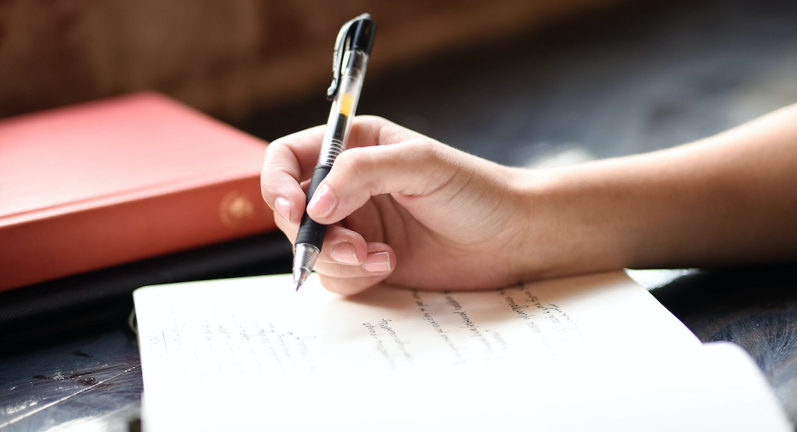 hand holding a pen above a pad with writing on it